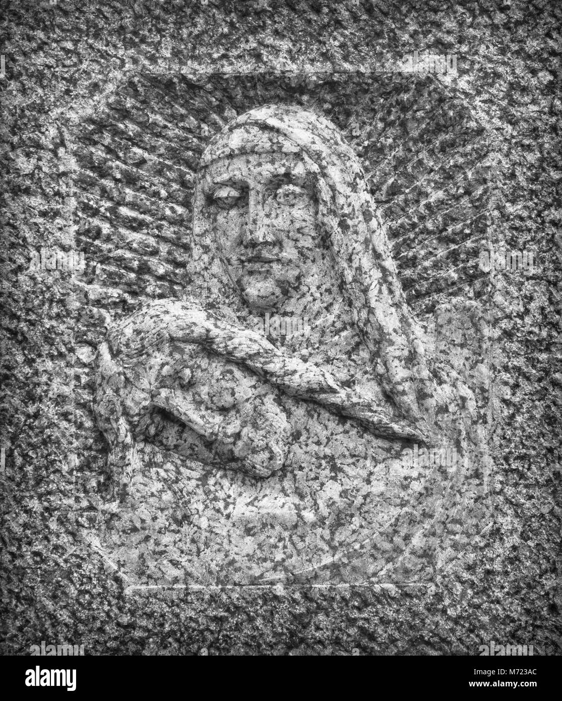 Bas-relief in stone representing The Pity of Michelangelo. Faces of Holy Mary mother and Jesus Christ after the - Stock Image