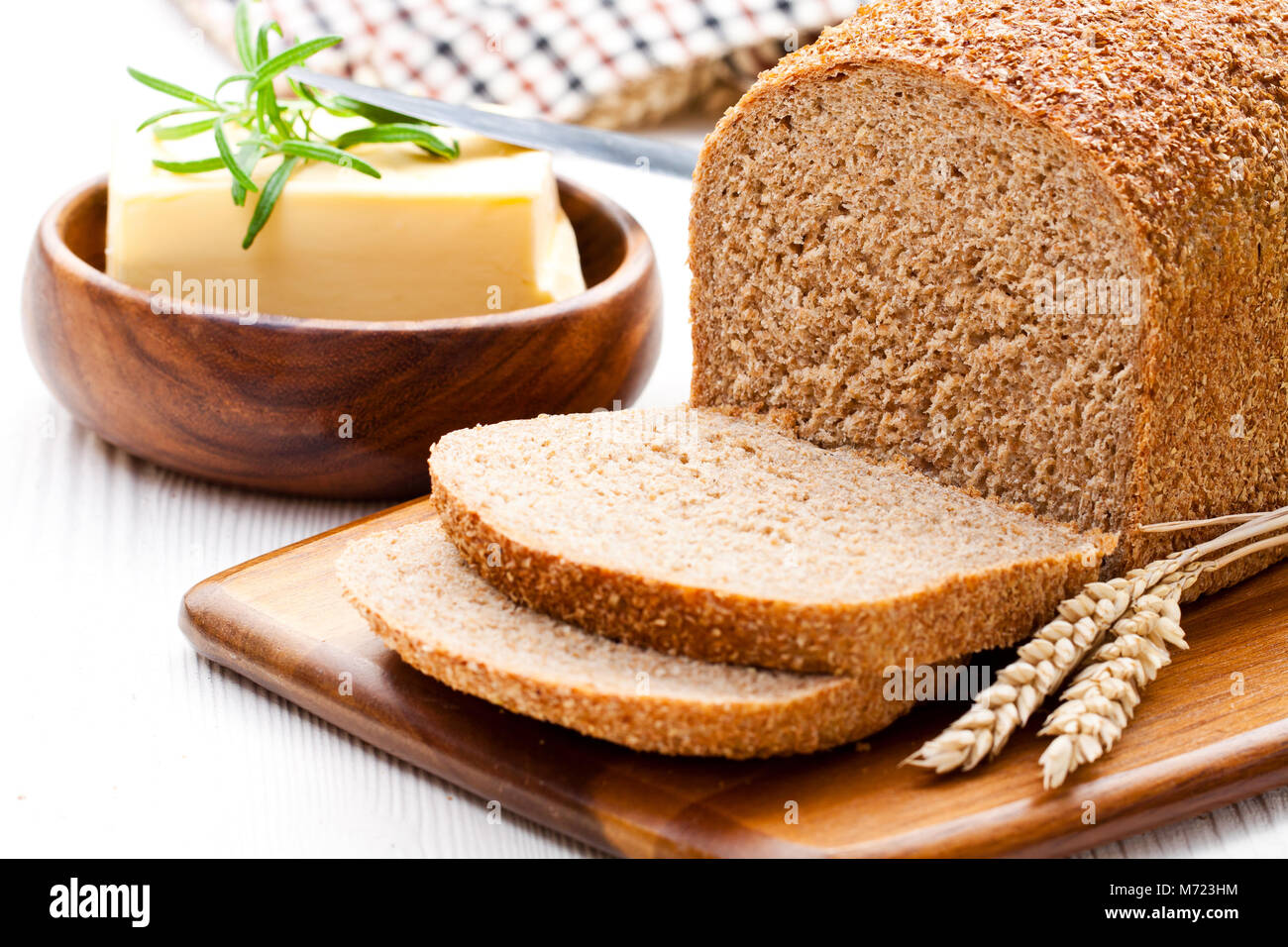 Sliced  slow-baked organic wholemeal bread with butter and rosemary and wheat ears - Stock Image