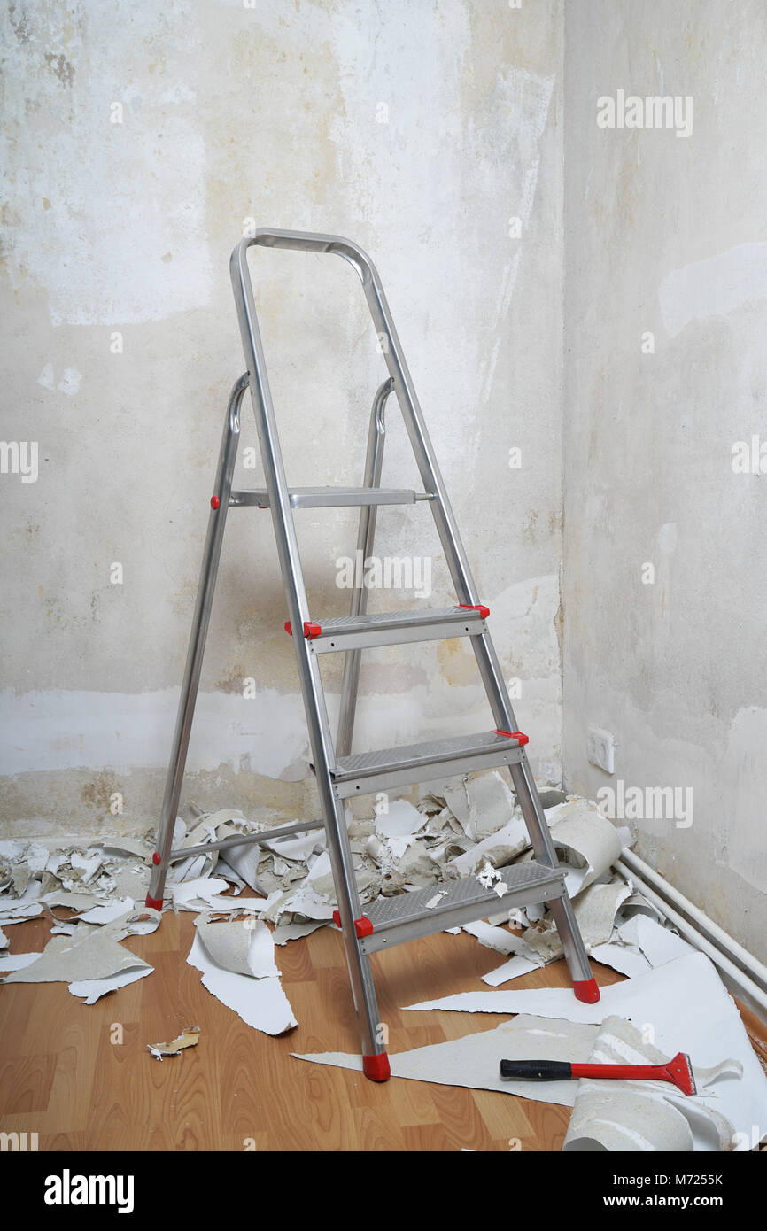 empty room with bare walls ladder and old wallpaper scraps on floor during redecoration - Stock Image