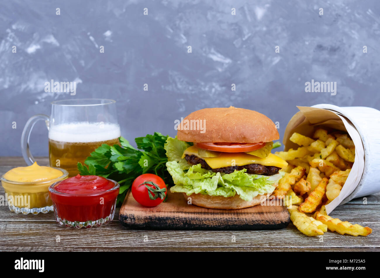 Juicy burger, french fries, sauces, beer  on a wooden background. Fast food. Street food. - Stock Image