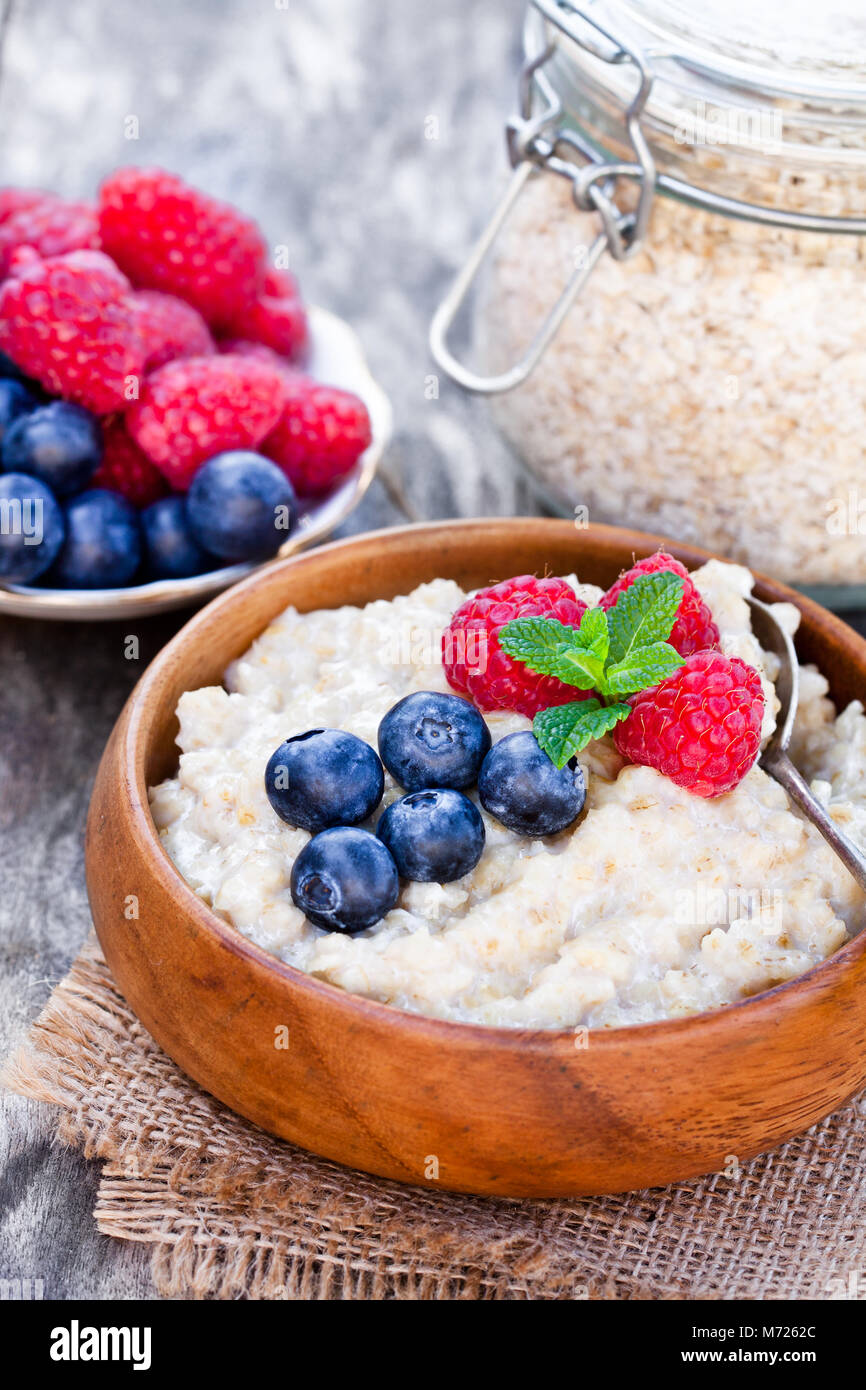 Porridge  in a wooden bowl with berries Stock Photo