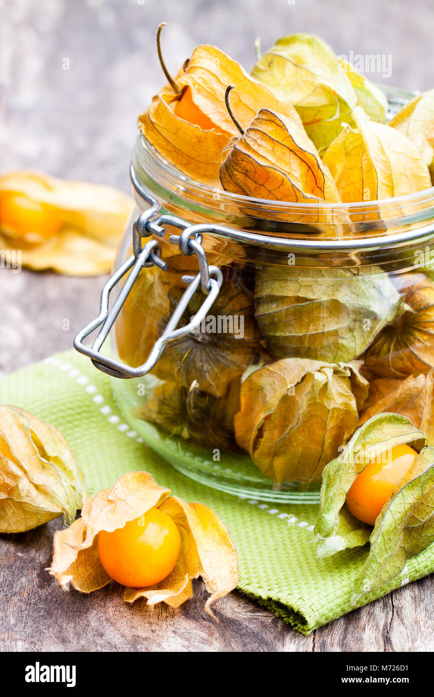 Ripe  physalis in a glass jar on wooden table - Stock Image