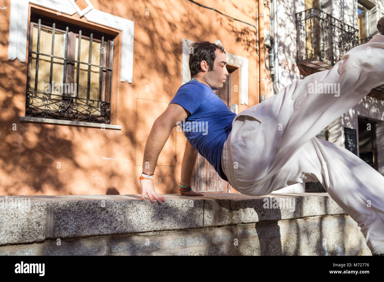 Young man doing an amazing parkour trick on the street. - Stock Image