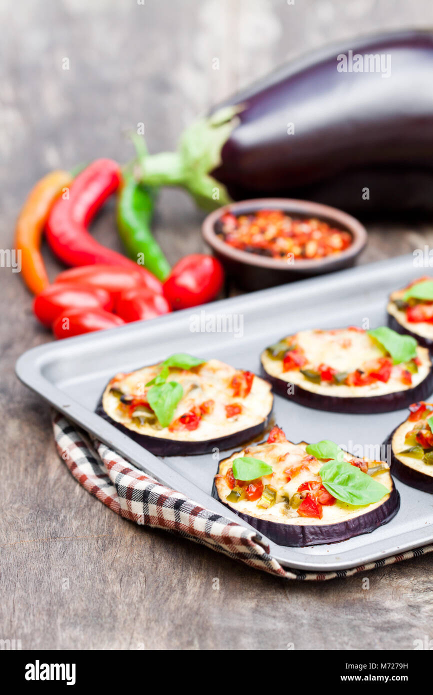 Baked  eggplant with cheese and tomatoes on baking tray - Stock Image