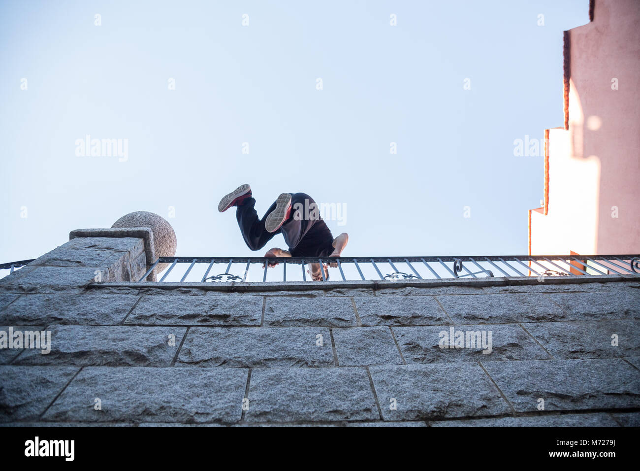Young man hanging on wall and trying to climb up while doing parkour. - Stock Image