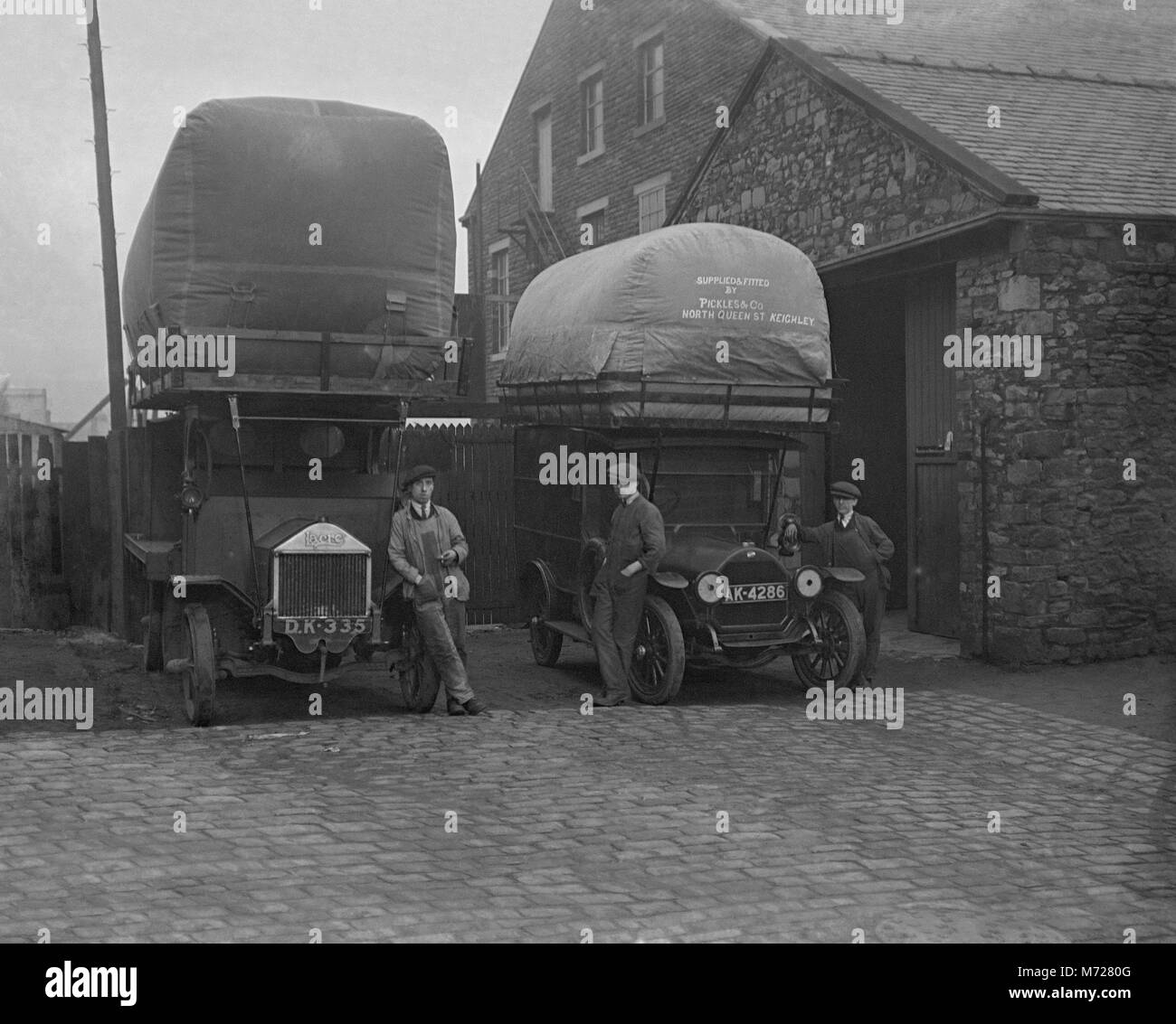 Two commercial vehicles and their drivers, West Yorkshire, England, UK c. 1917. They each have a massive bag containing - Stock Image