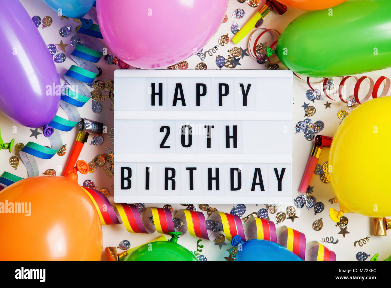 Happy 20th birthday celebration message on a lightbox with balloons and confetti - Stock Image