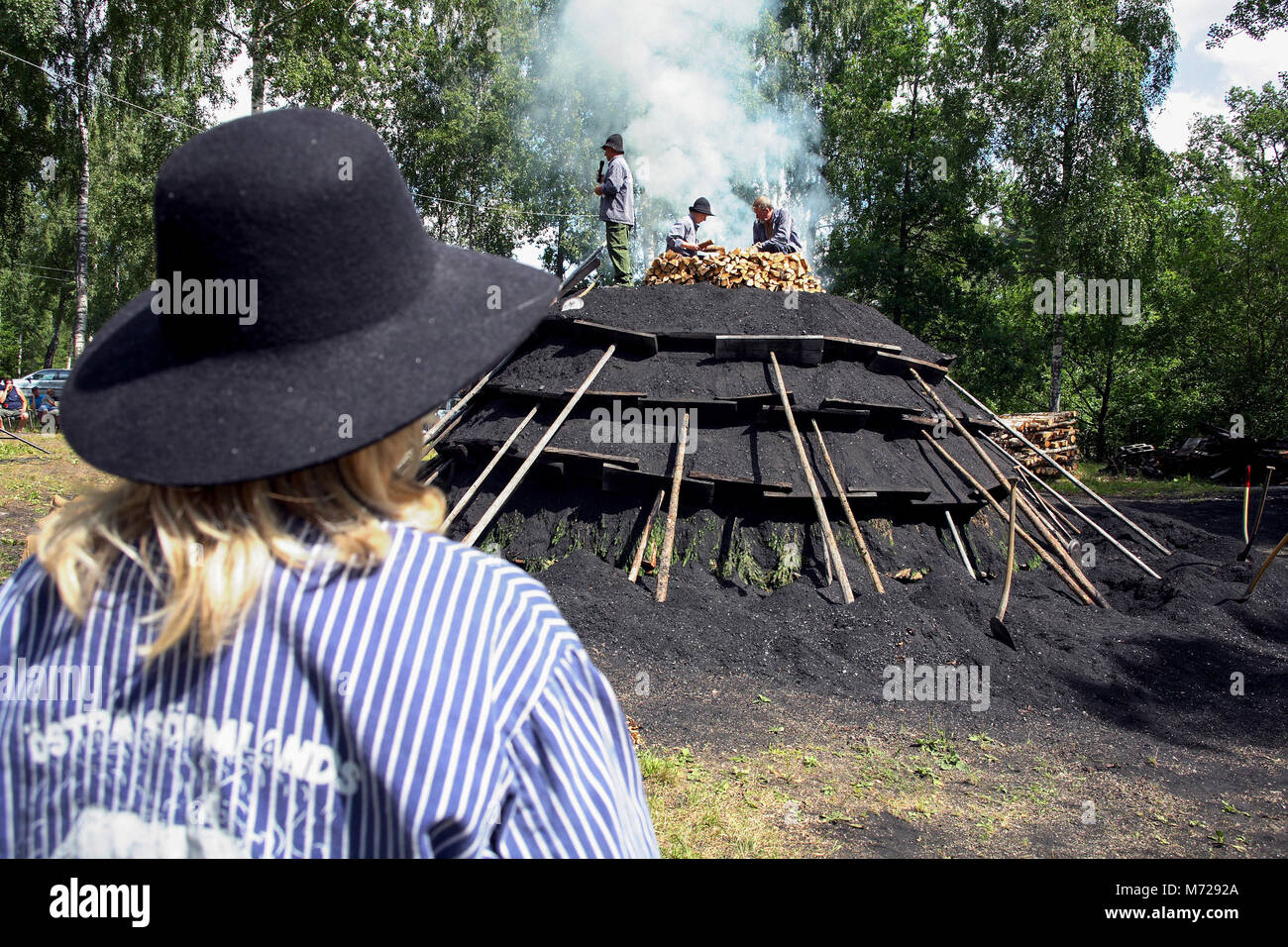 CHARCOAL BURNERS start a Charcoal stack - Stock Image
