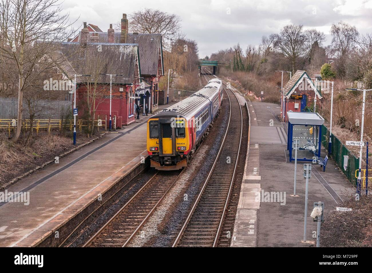 A Class 156 diesel multiple unit train passing through the rural station at Sankey in Cheshire. East Midlands Trains - Stock Image