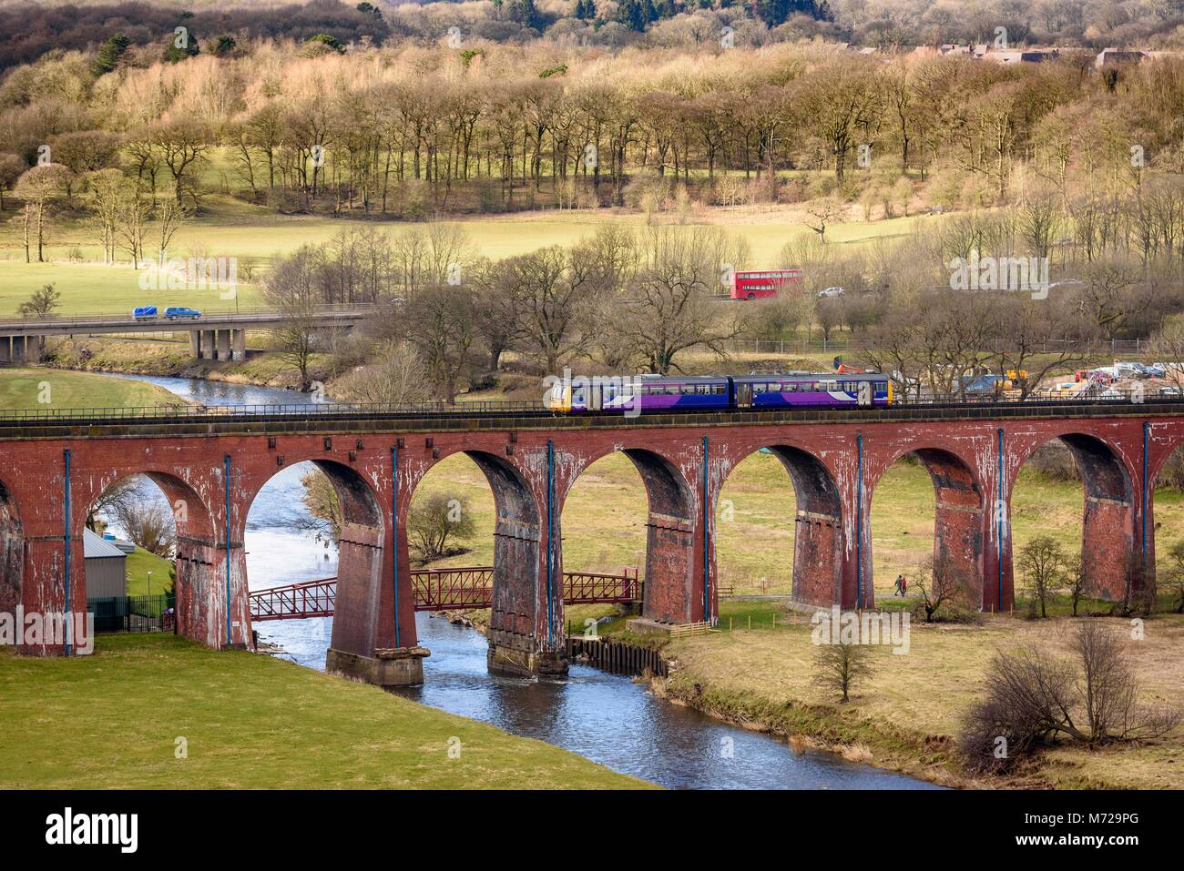 A Pacer diesel multiple unit train crossing the Whalley Arches viaduct over the river Calder. - Stock Image