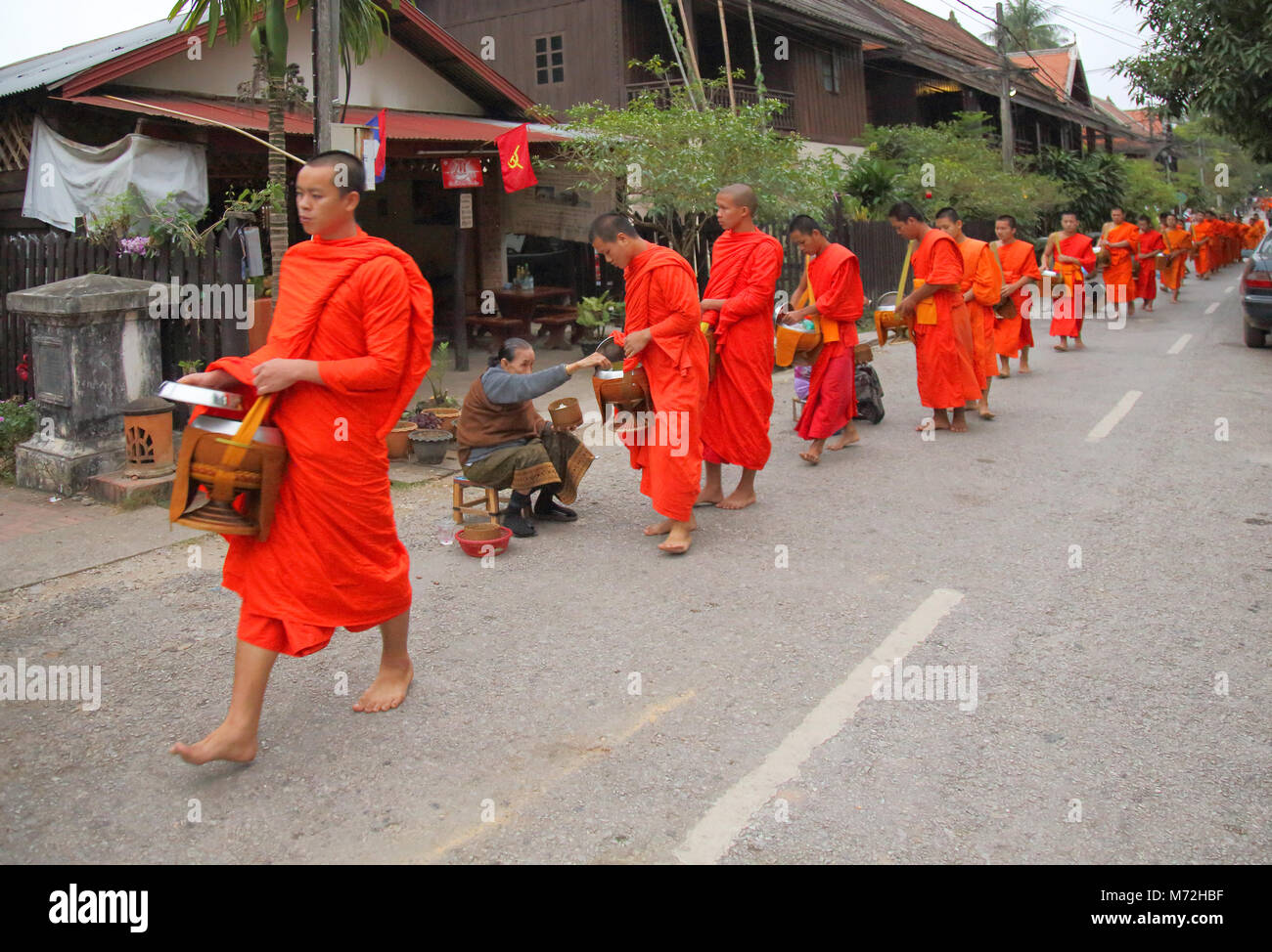 buddhist monks collectilg alms at daybreak in luang prabang laos - Stock Image