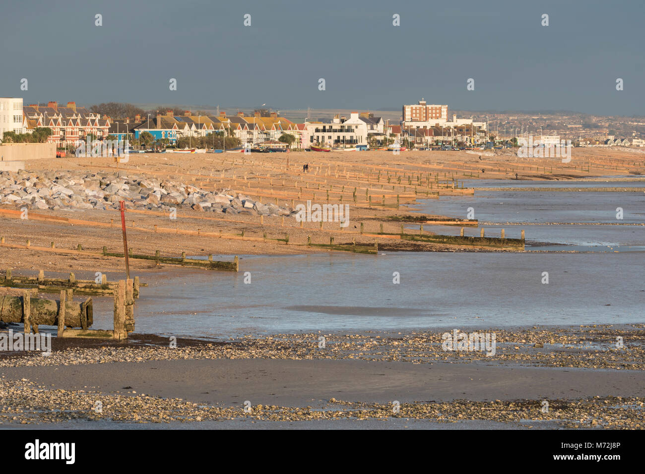 Landscape view of the seafront coastline on a well lit day with dark clouds in Worthing, West Sussex, England, UK. - Stock Image