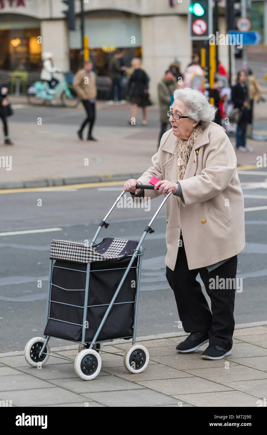 Elderly lady pushing a wheeled shopping trolley at shops in the UK. - Stock Image