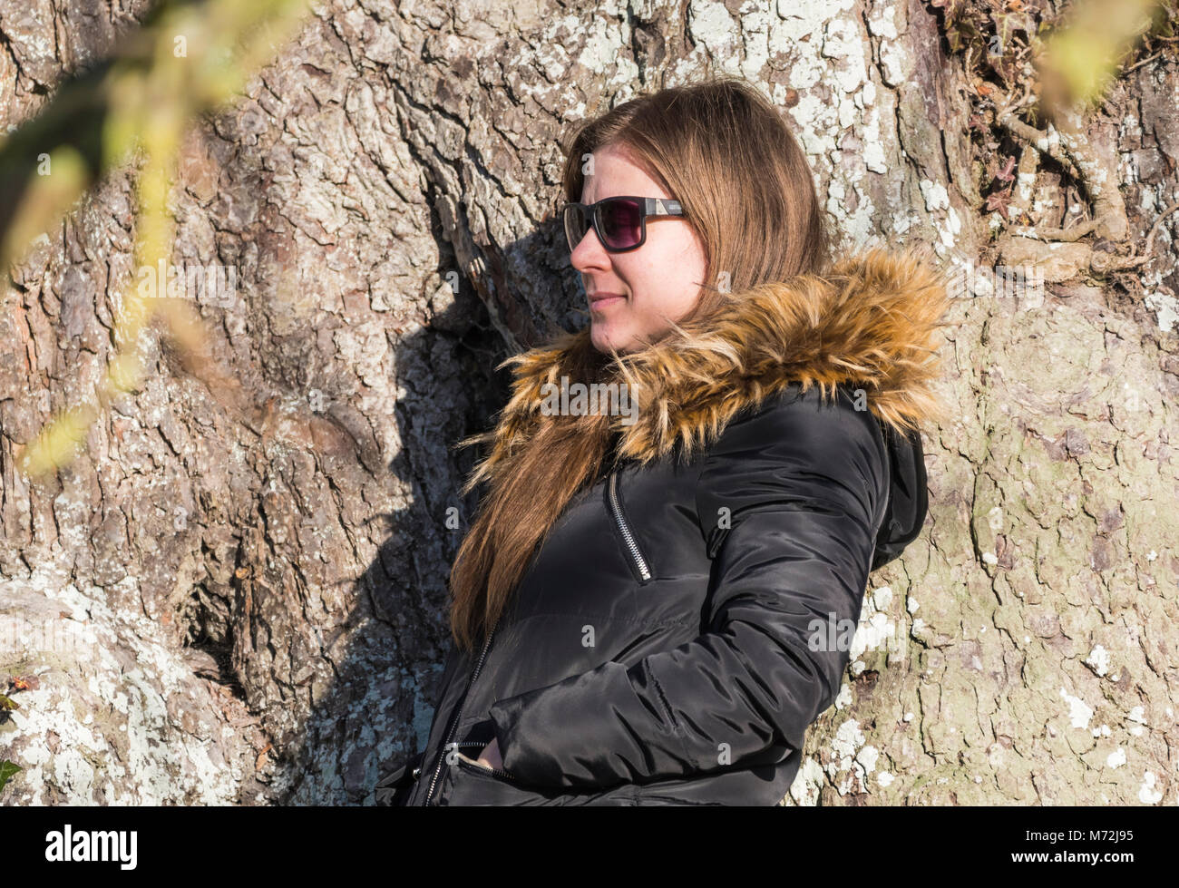 Pretty young woman posing by a tree outside in Winter having her photo taken. - Stock Image
