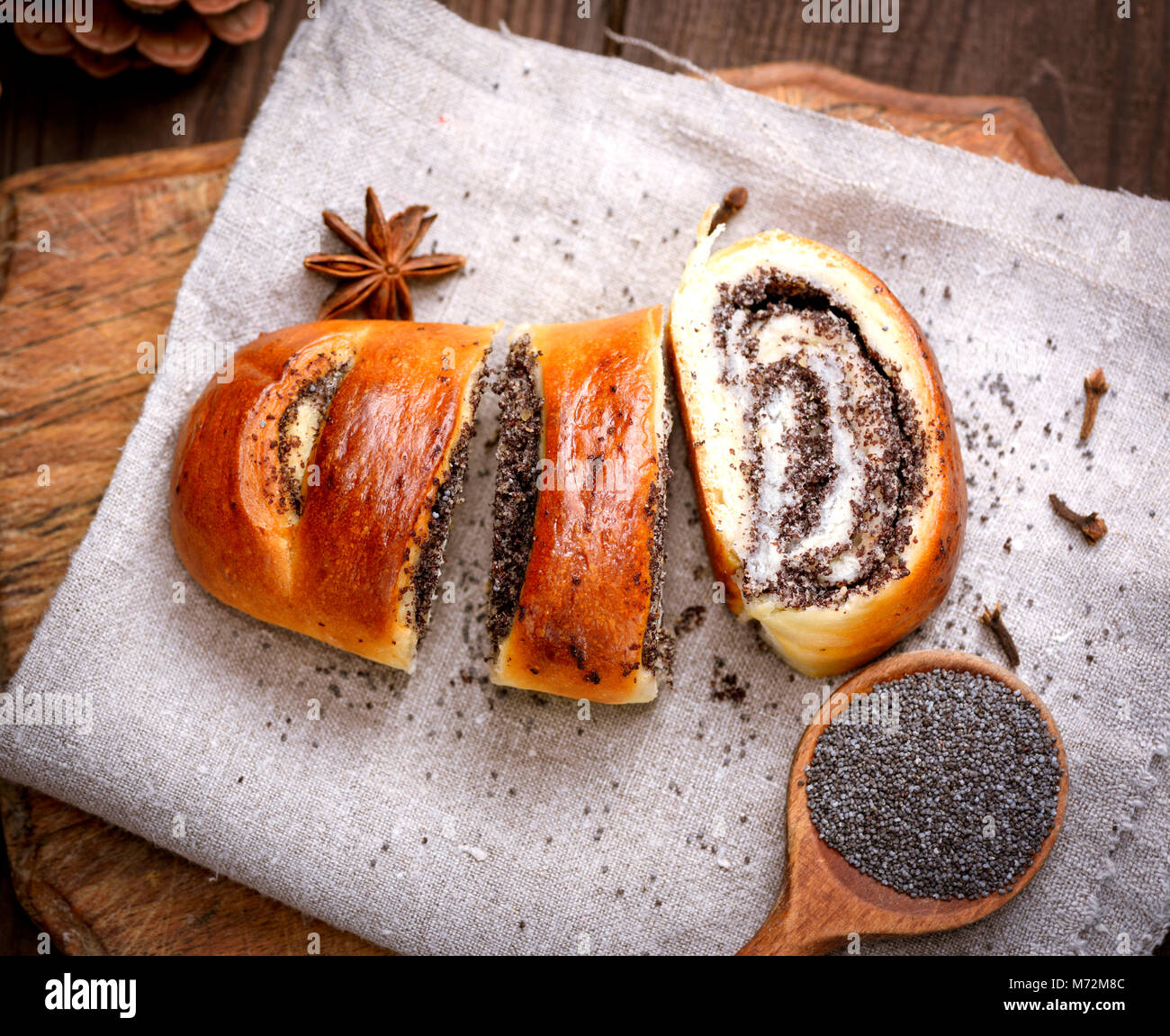 baked roll with poppy seeds on a wooden board, top view - Stock Image