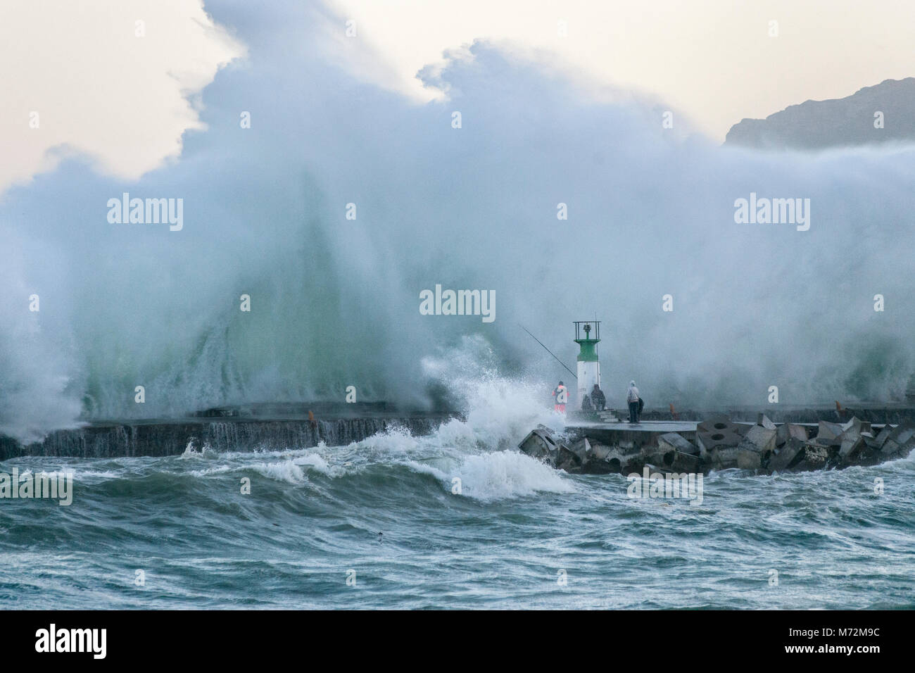 Fishermen braving enormous waves that are seen here crashing up against the breakwater of Kalk Bay harbour in Cape Town, South Africa. Stock Photo