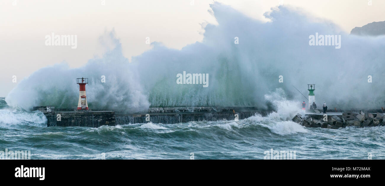 Fishermen braving enormous waves that are seen here crashing up against the breakwater of Kalk Bay harbour in Cape - Stock Image