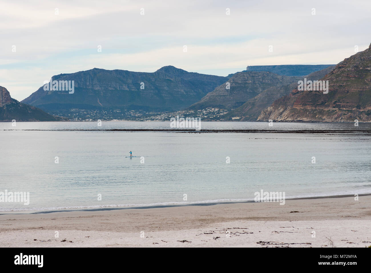 Stand up paddle boarder off Long Beach in Kommetjie, Cape Town. - Stock Image