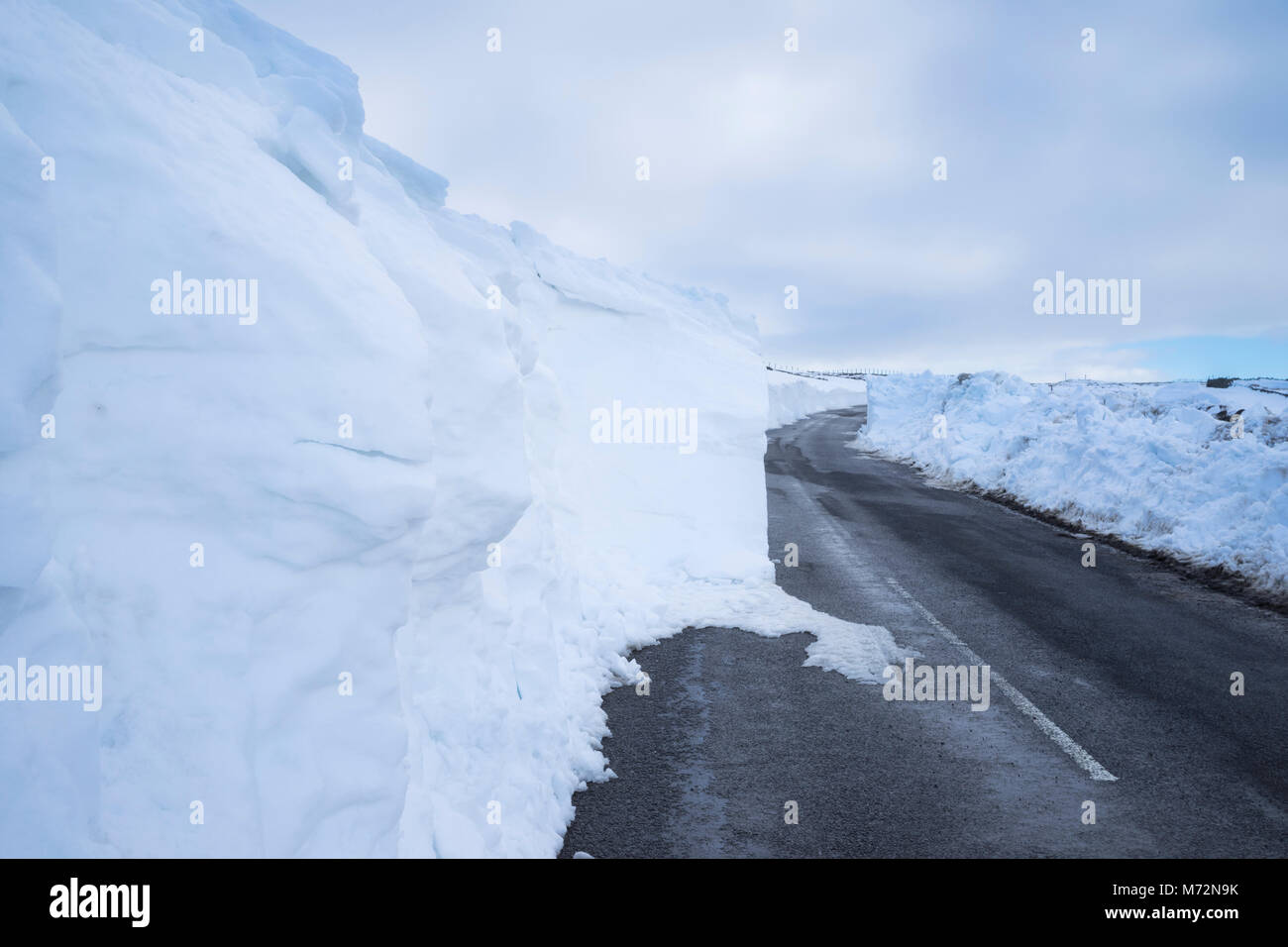 Country road near Allenheads in the North Pennines Area of Outstanding Natural Beauty, partially blocked by snow - Stock Image