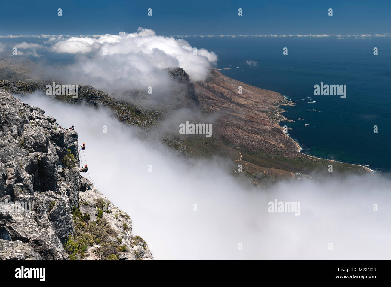 Abseilers abseiling off the summit of Table Mountain with Cape Town's Atlantic coastline in the background. Stock Photo