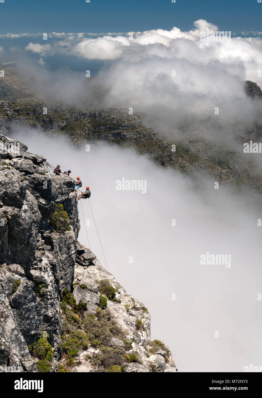 Abseilers abseiling off the summit of Table Mountain in Cape Town with the cloud-shrouded Twelve Apostles mountains Stock Photo