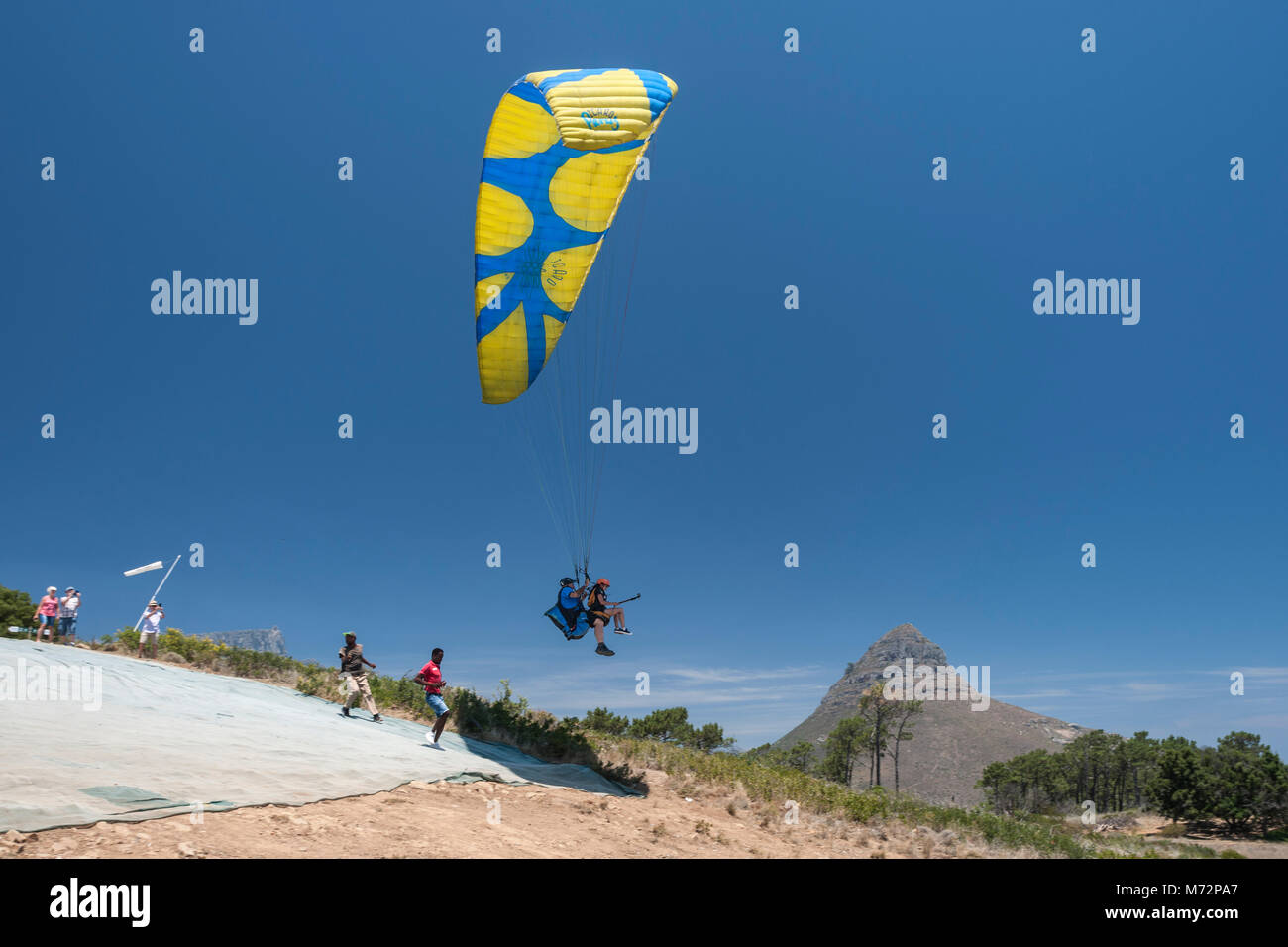 Tandem paraglider launching off the slopes of Signal Hill in Cape Town. Lion's Head and Table Mountain can be seen - Stock Image