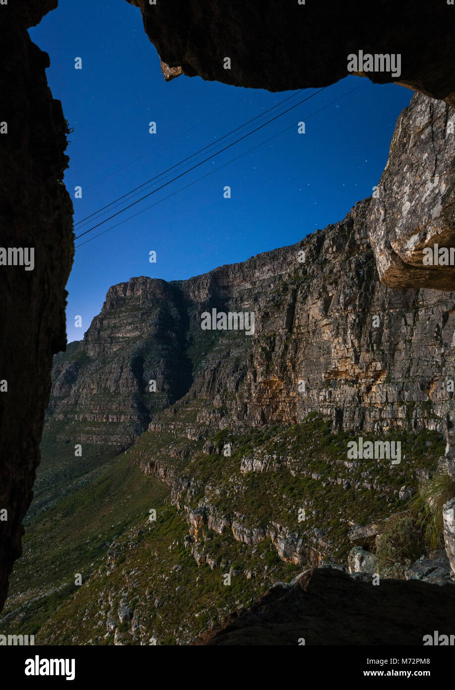 Table Mountain (in moonlight) seen through a natural rock formation called India Venster. - Stock Image
