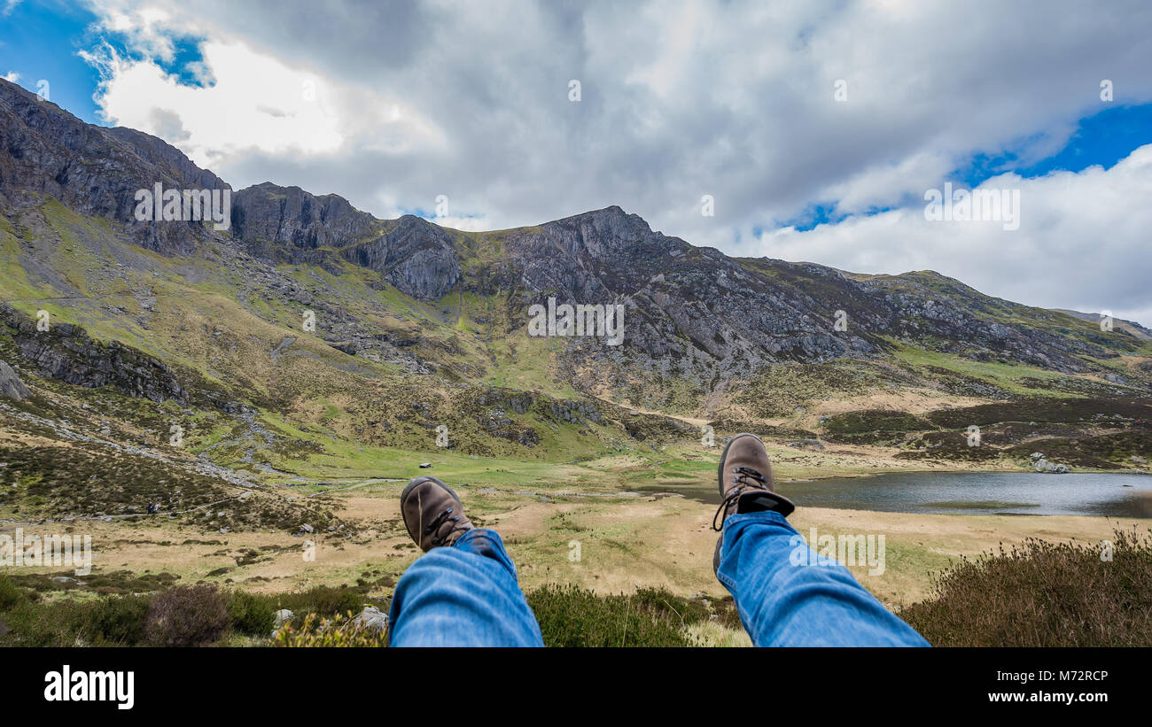 Hiker Resting on Mountainside with View and Hiker's Boots - Unplugged - Stock Image