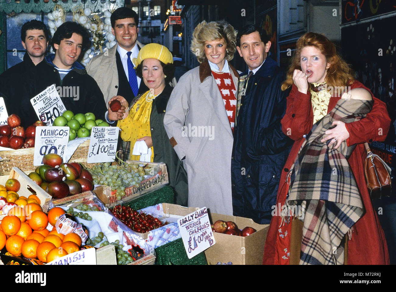 A group of British Royal Family look-alikes at a fruit market stall. London. England, UK - Stock Image