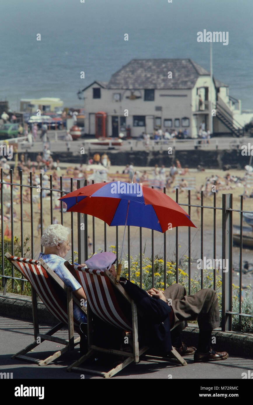 Mature couple relaxing in the sunshine at  Broadstairs, Kent, England, UK - Stock Image