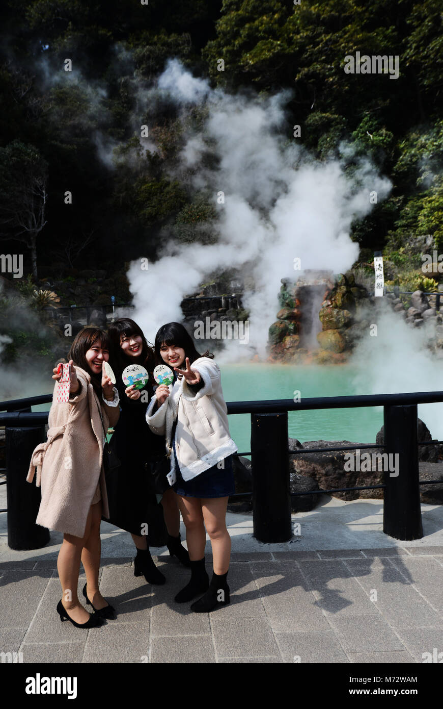 Tourist posing for a photo in front of the Umi Jigoku ( Ocean Hell ) hot spring in Beppu, Japan. - Stock Image