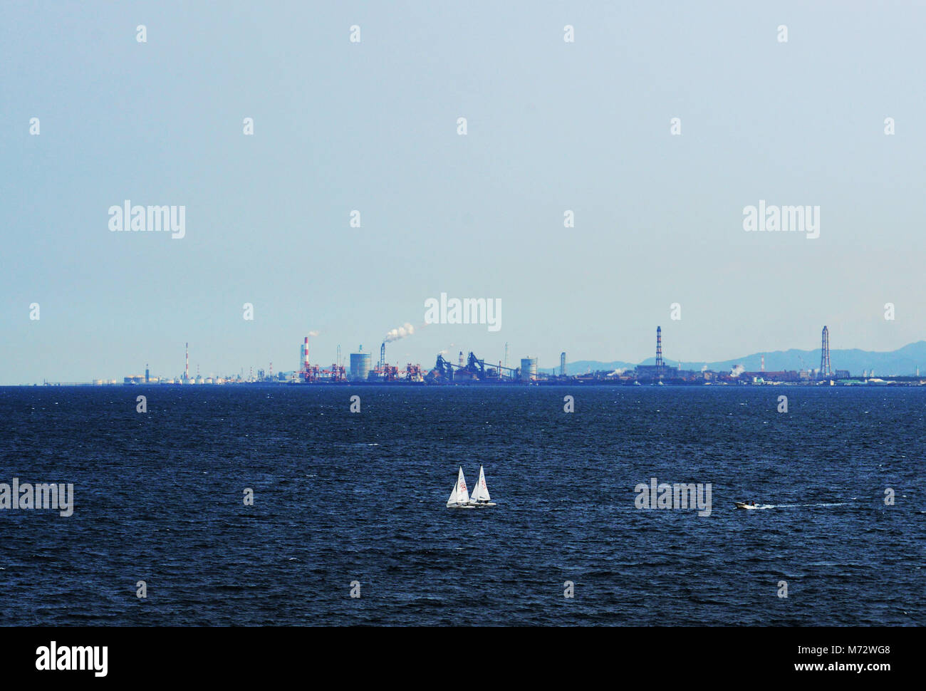 Sailboats sailing in Beppu bay. The Oita port in the background. - Stock Image