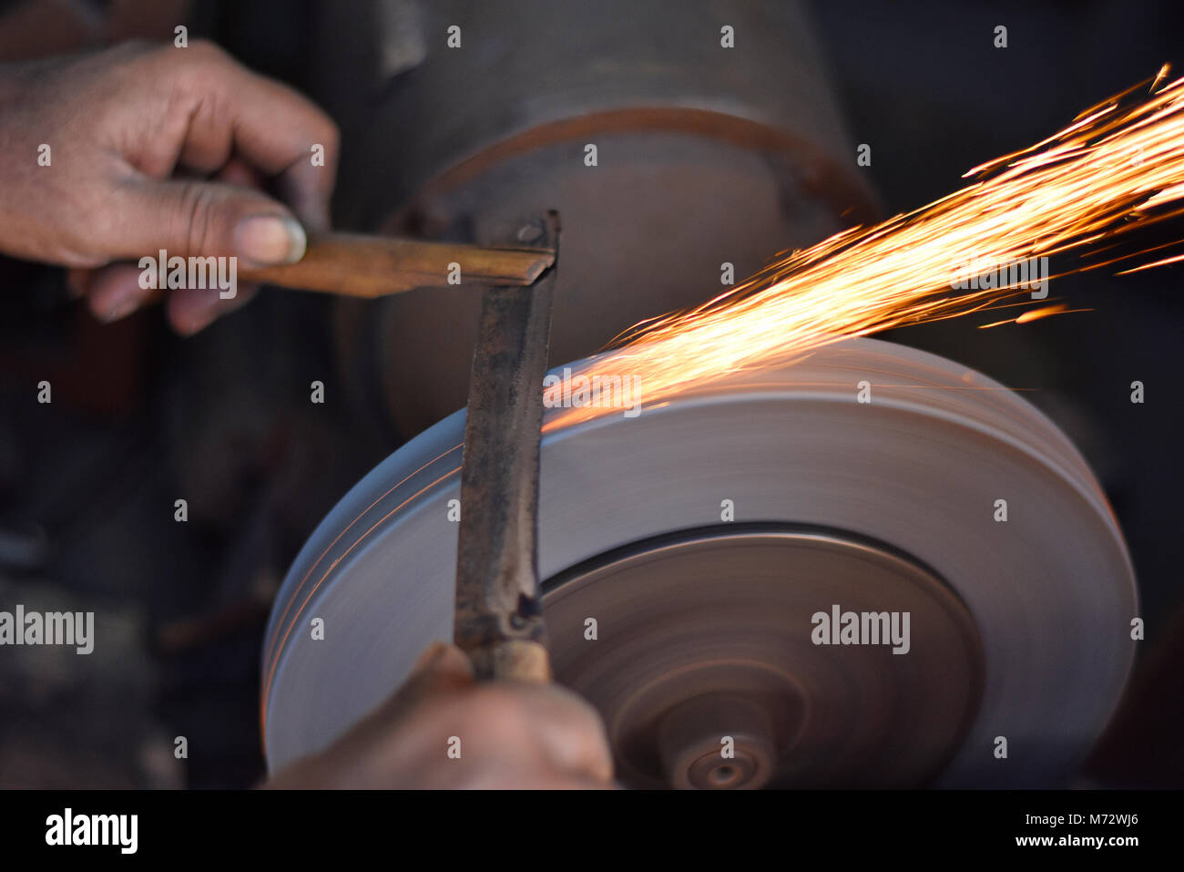 Man grinding on abrasive cutting and knife-sharpening stones. Mumbai, Maharashtra, India - Stock Image