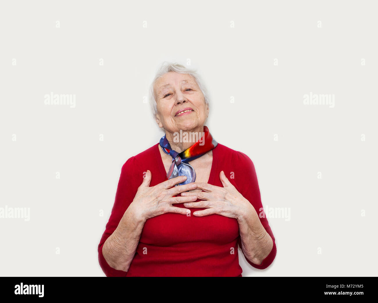Happy smiling retired senior woman looking at camera isolated on white background - Stock Image