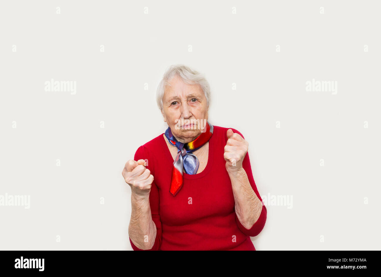 Angry old woman making fists on white background - Stock Image