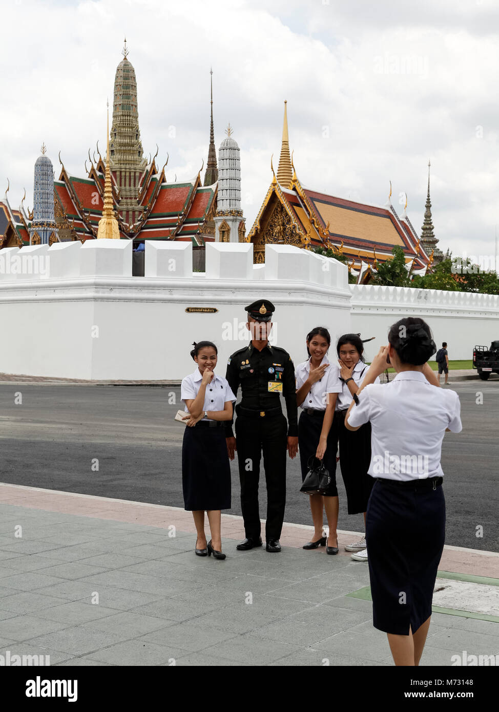 Girls taking picture with a Thai army officer with the Grand Palace of Bangkok in the background - Stock Image