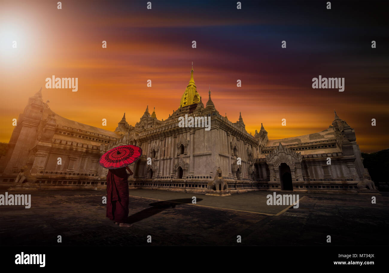 Asian young monk holding red umbrella on the Ananda temple at sunset in Bagan, Myanmar. - Stock Image