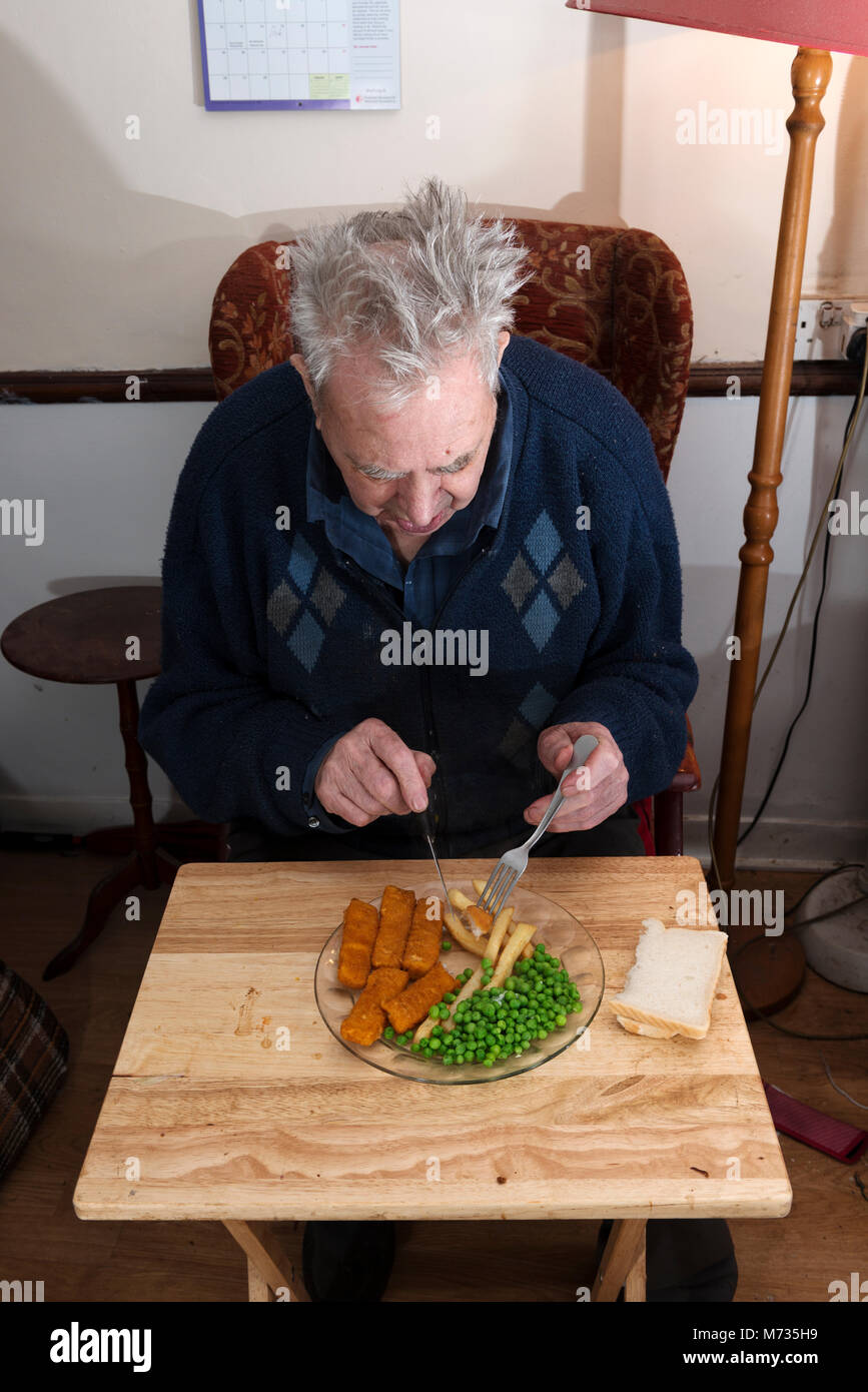 Elderly man living alone eating fish fingers, chips and peas for lunch - Stock Image