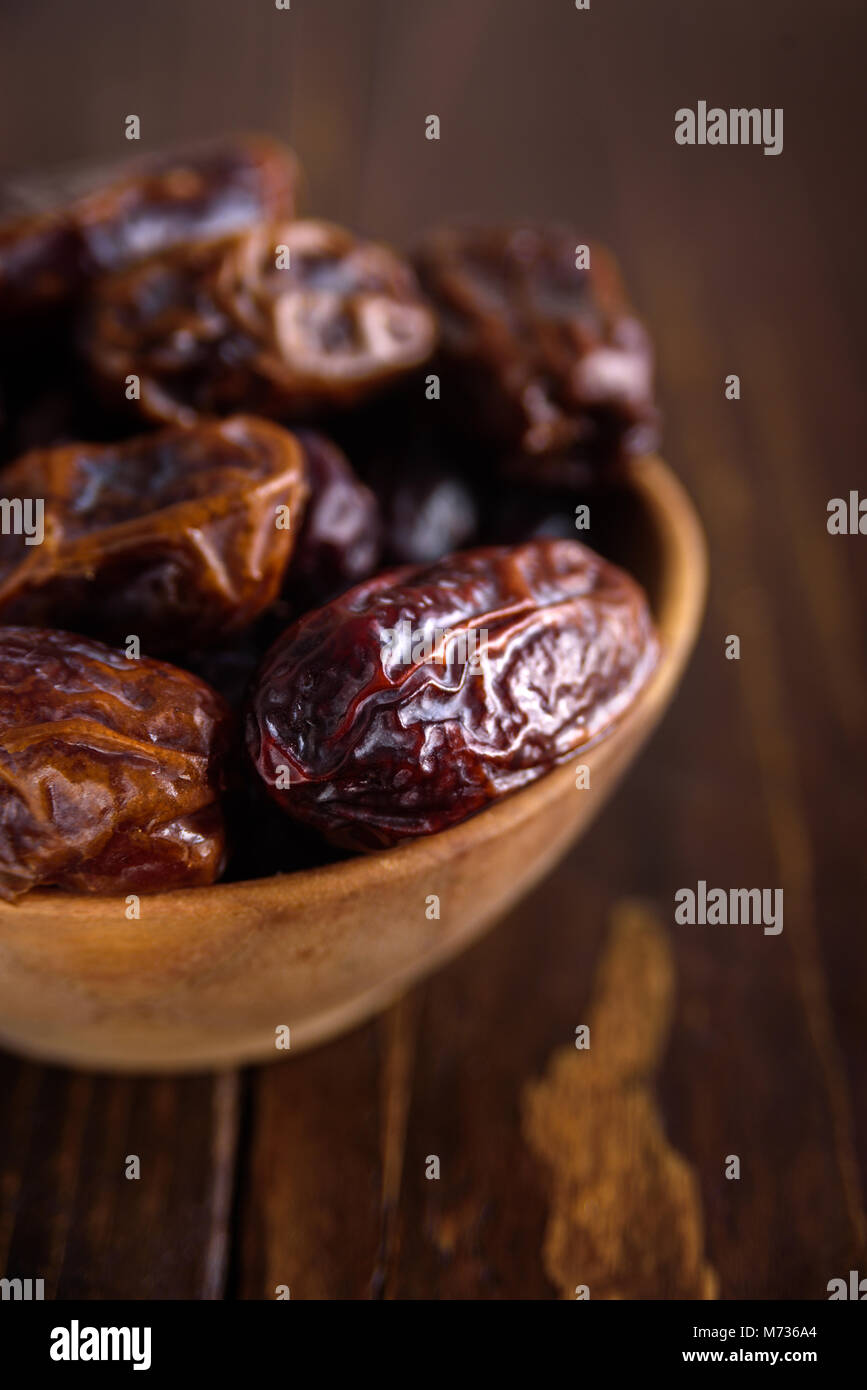 Fresh dates fruit in wooden bowl on wooden background - Stock Image