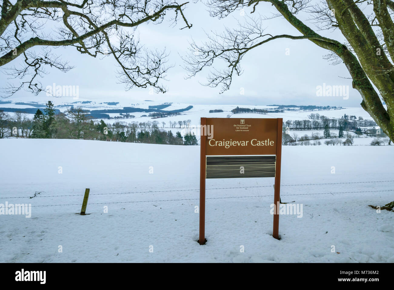 CRAIGIEVAR CASTLE ABERDEENSHIRE SCOTLAND A SIGN INDICATING THE CASTLE OVERLOOKING THE WINTER FIELDS AND COUNTRYSIDE - Stock Image