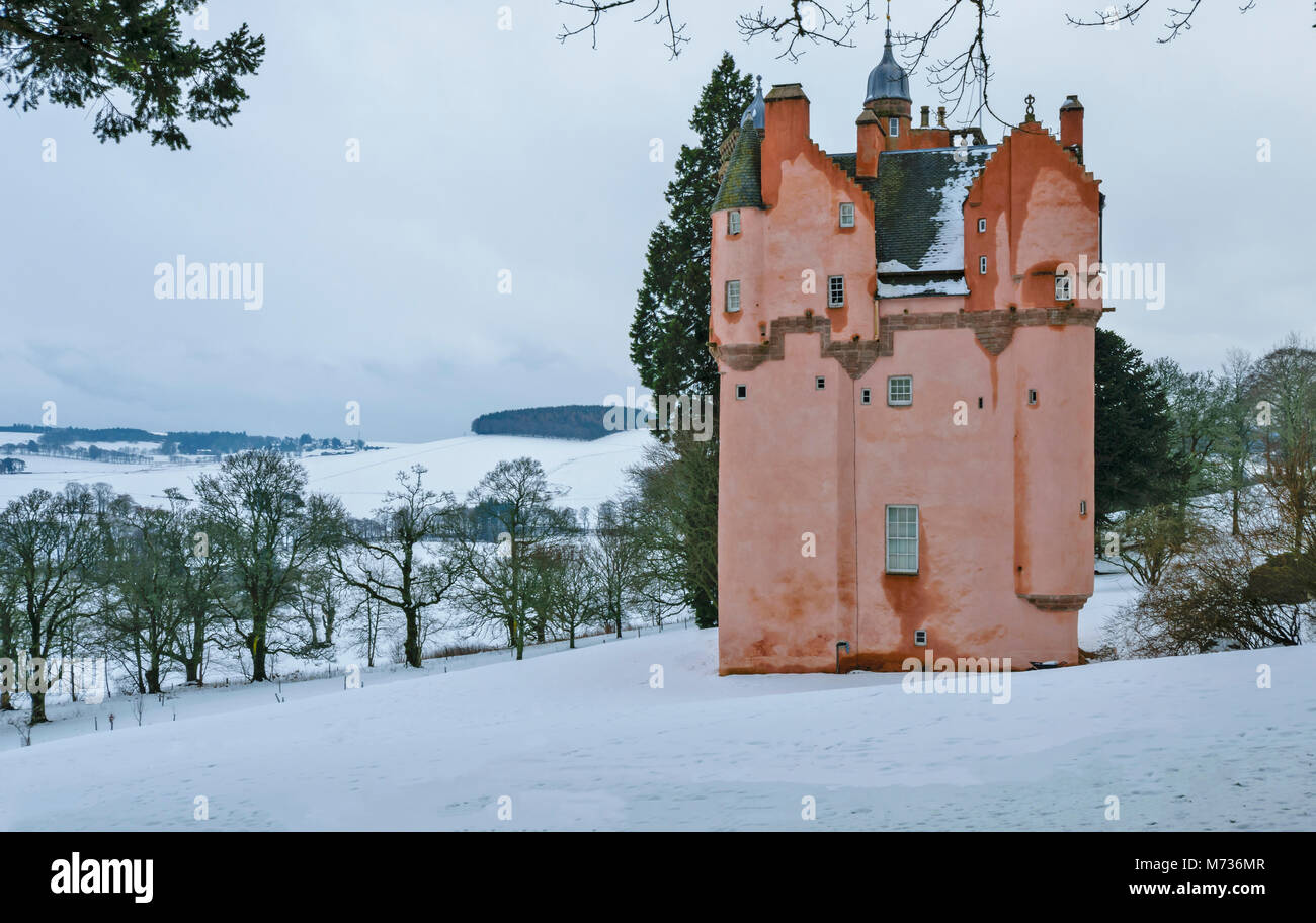 CRAIGIEVAR CASTLE ABERDEENSHIRE SCOTLAND PINK TOWER ON A SNOW COVERED HILL WITH TREES OVERLOOKING THE WINTER COUNTRYSIDE - Stock Image