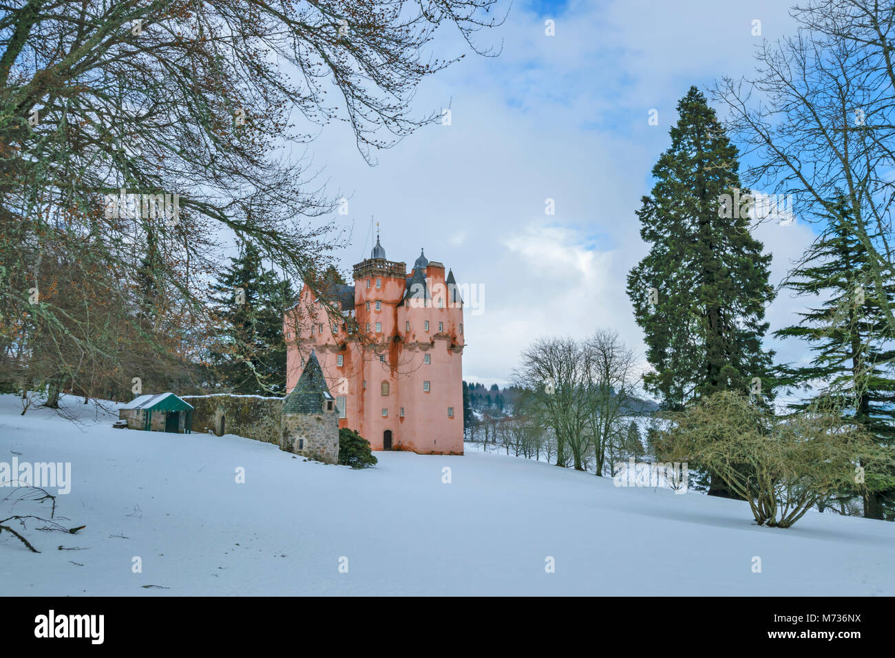 CRAIGIEVAR CASTLE ABERDEENSHIRE SCOTLAND SURROUNDED BY WINTER SNOW WITH BEECH AND EVERGREEN PINE TREES - Stock Image