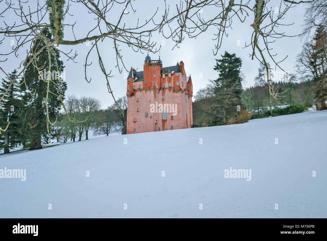 CRAIGIEVAR CASTLE ABERDEENSHIRE SCOTLAND THE PINK TOWER ON A SNOW COVERED HILL IN WINTER - Stock Image