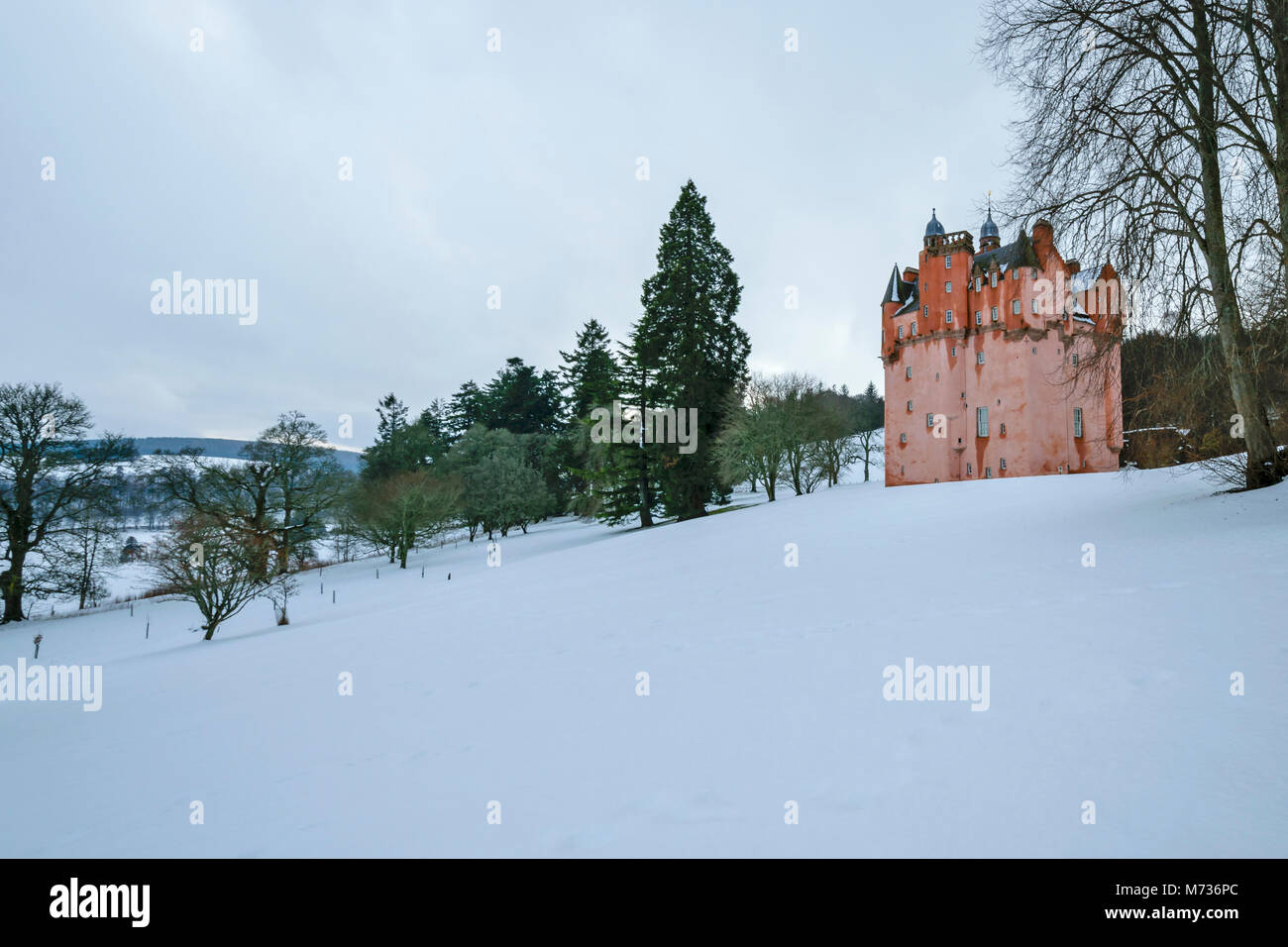 CRAIGIEVAR CASTLE ABERDEENSHIRE SCOTLAND THE PINK TOWER ON A SNOW COVERED HILL OVERLOOKING THE WINTER COUNTRYSIDE - Stock Image