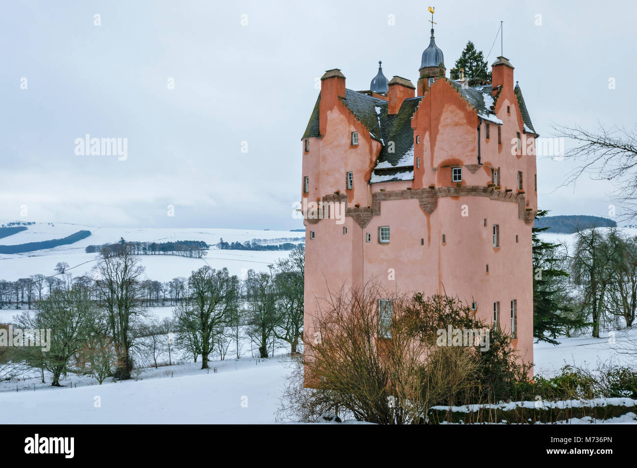 CRAIGIEVAR CASTLE ABERDEENSHIRE SCOTLAND THE PINK TOWER ON A SNOW COVERED HILL WITH TREES OVERLOOKING THE WINTER - Stock Image