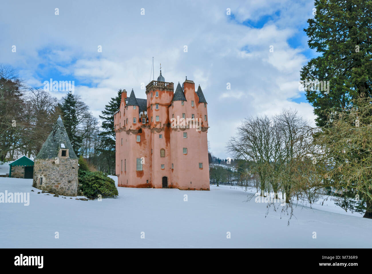 CRAIGIEVAR CASTLE ABERDEENSHIRE SCOTLAND WITH THE PINK TOWER SURROUNDED BY WINTER SNOW  AND EVERGREEN PINE TREES - Stock Image