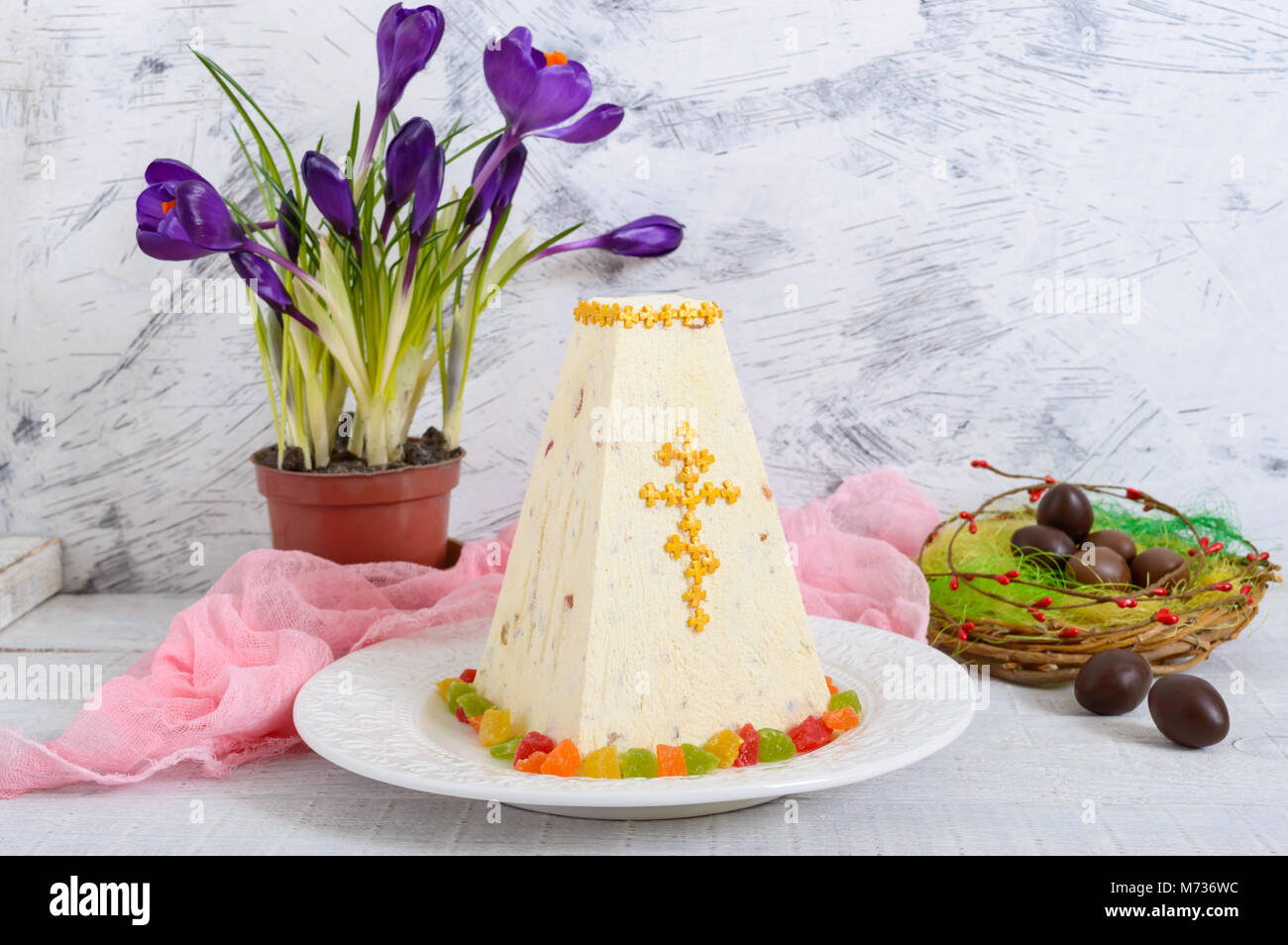 Traditional curd Easter cake with candied fruits and chocolate eggs, spring flowers crocus on the holiday light Stock Photo