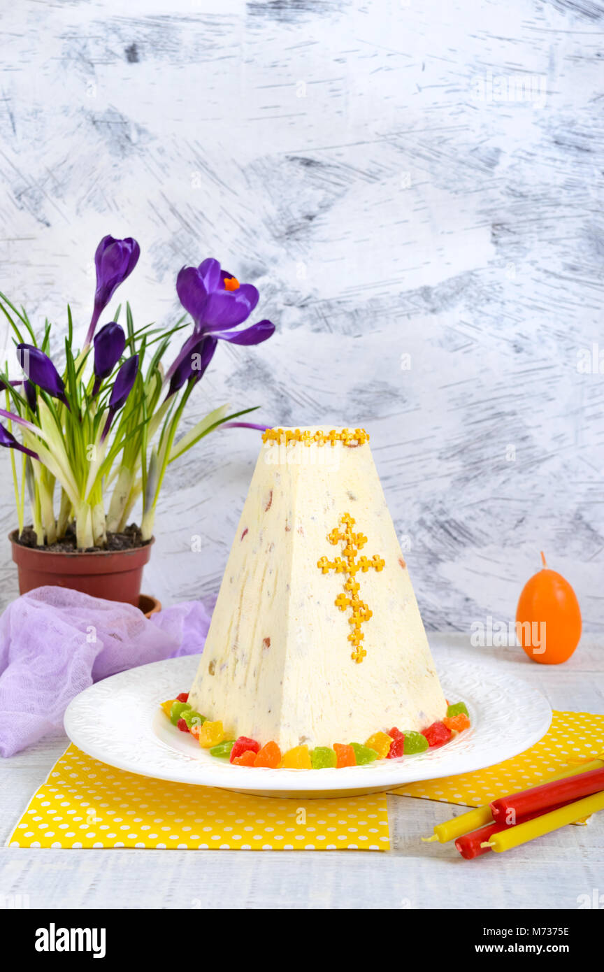 Traditional curd Easter cake with candied fruits and spring flowers crocus on the holiday light background. Easter - Stock Image