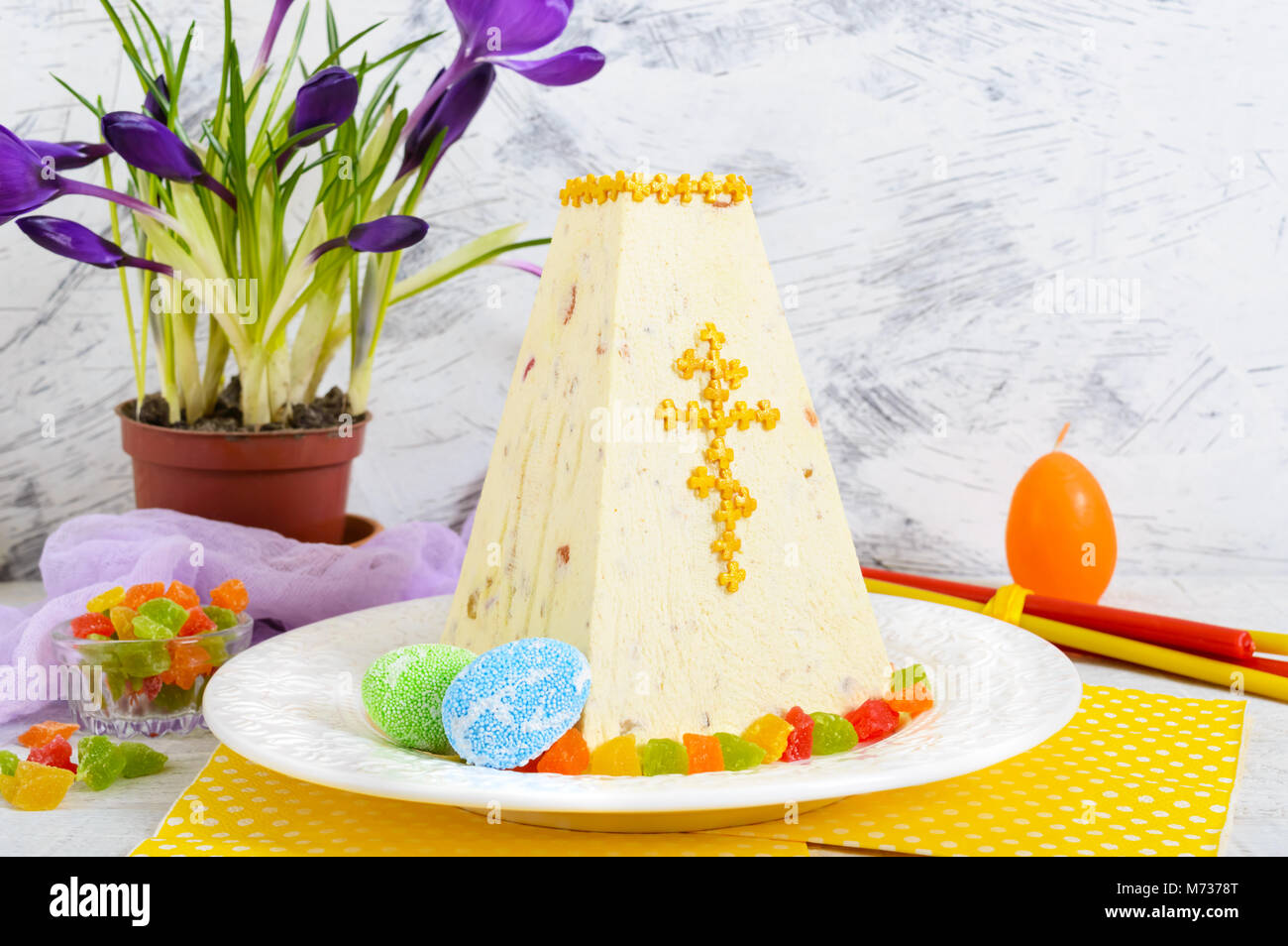 Traditional curd Easter cake with candied fruits and spring flowers crocus on the holiday light background. Easter Stock Photo