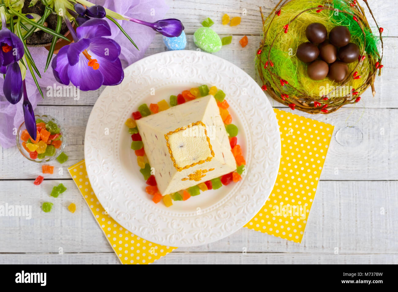 Traditional curd Easter cake with candied fruits and chocolate eggs, spring flowers crocus on the holiday light - Stock Image